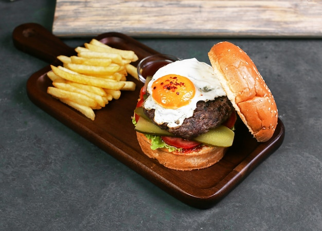 Burger with fried egg, meat and vegetables.