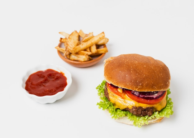 Burger with fries and ketchup on white table