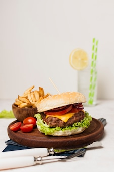 Burger with fries on wood plate