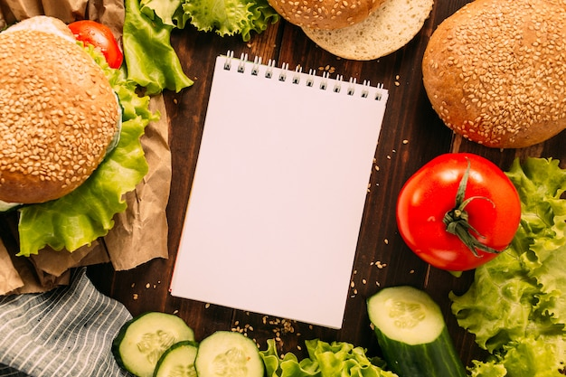 Burger with ingredients and notepad on table