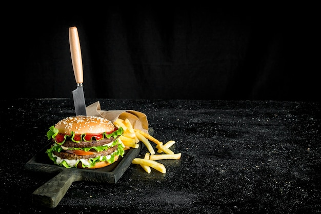 Burger with a knife and fries. on rustic background