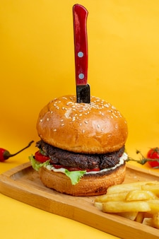 Burger with knife inside and fries