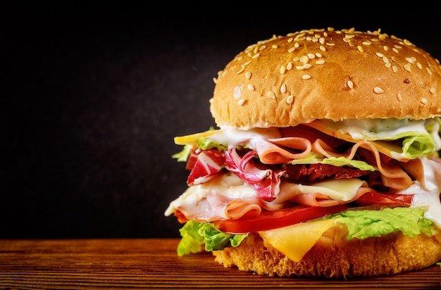 Burger with lettuce, cheese, ham and tomato on dark background.