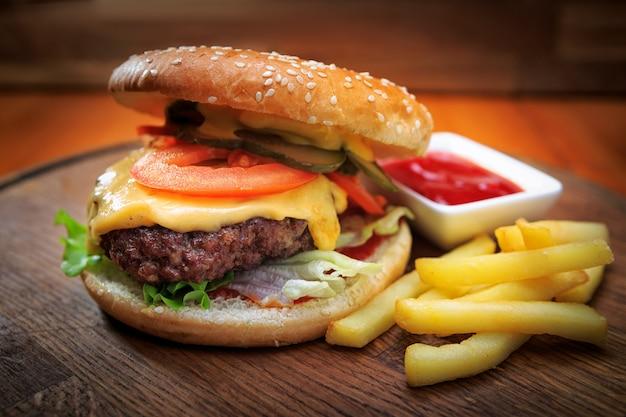 Бургер с мясом и жареным картофелем на деревянной доске