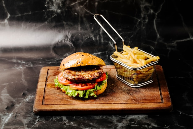 Burger with meat , tomato and lettuce served with french fries.