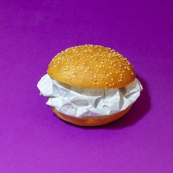 紫色の背景に紙とハンバーガー。抽象化。アイディア。