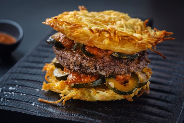 Burger with potato patties and stuffed zucchini served on board on dark background. closeup