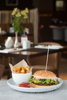 Бургер с салатом и соусом на бетонном столе, фоне ресторана. большой бургер с картофельным айдахо и кетчупом