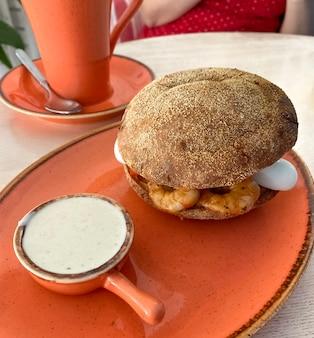 エビ、卵のハンバーガー。シーザードレッシングとプレートのサンドイッチ