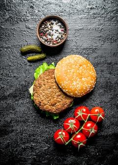 토마토, 오이, 시골 풍 테이블에 향신료와 햄버거.