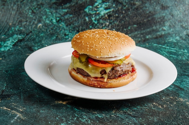 Burger with vegetables and meat inside bread bun.