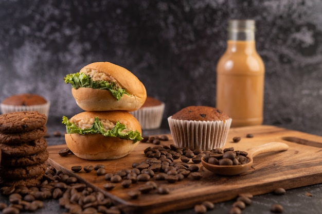Burger with wooden cutting board, including cupcakes and coffee beans.
