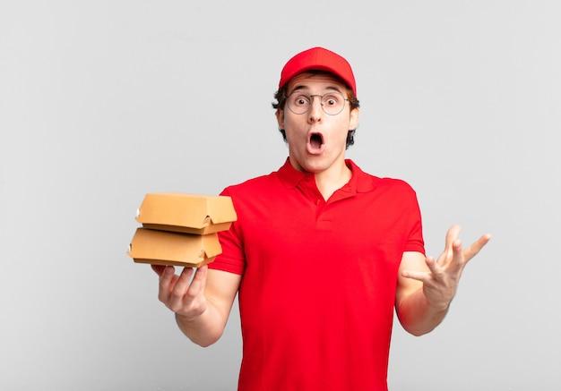 Бургеры доставляют мальчика, который чувствует себя чрезвычайно шокированным и удивленным, встревоженным и паническим, с напряженным и испуганным взглядом.