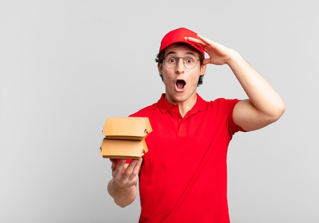 Burgers deliver boy looking happy, astonished and surprised, smiling and realizing amazing and incredible good news