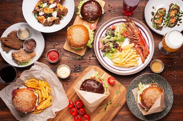 ハンバーガー、フライドポテト、サラダ、エビのグリル、ソース、ビール、その他の飲み物を木製のテーブルでお召し上がりいただけます。上面図の水平方向のショット。