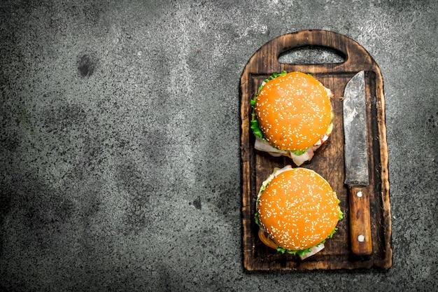 素朴な背景のまな板に新鮮な牛肉と野菜のハンバーガー