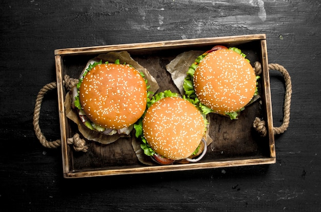 Burgers on an old tray on the black chalkboard