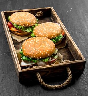 黒い黒板の古いトレイのハンバーガー