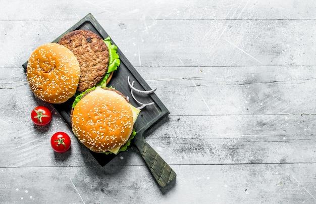Гамбургеры на черной разделочной доске с ломтиками лука и помидорами на белом деревянном столе