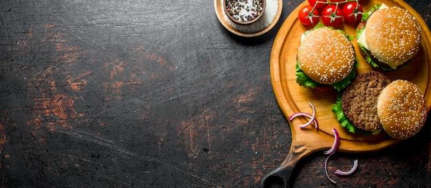 어두운 시골 풍 테이블에 향신료와 토마토 라운드 커팅 보드에 햄버거