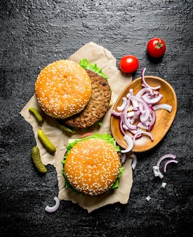 Burgers on paper with chopped onion in bowl and tomatoes. on black rustic background