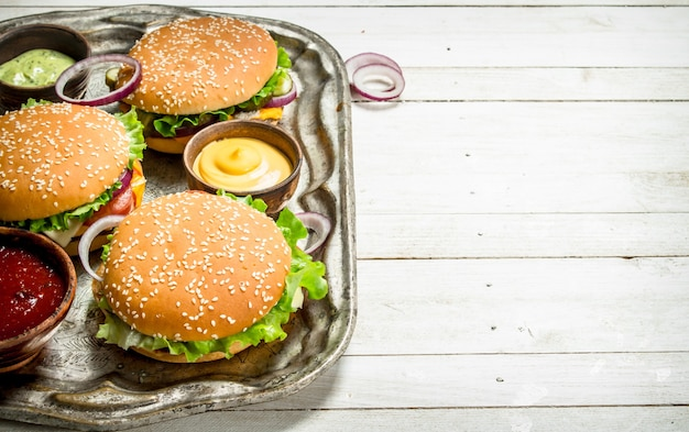白い木製の背景の上の鋼のトレイに牛肉と野菜のハンバーガー