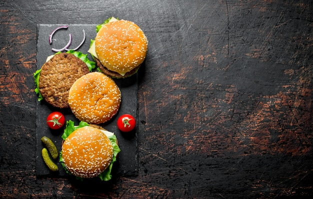Burgers with beef,tomatoes and cucumbers. on black rustic background