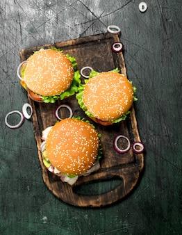 素朴な背景の古いボードに牛肉、野菜、甘い玉ねぎのハンバーガー