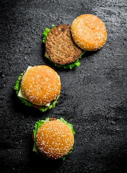 Burgers with beef and vegetables. on black rustic background