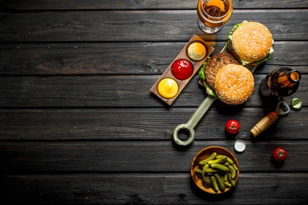 Burgers with beer,gherkins and sauces. on black wooden background