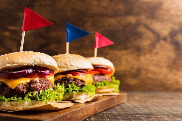 Burgers with colored flags on wooden tray