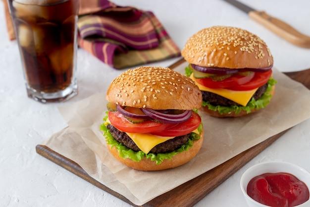 カツレツ、トマト、レタス、きゅうり、玉ねぎ、チーズのハンバーガー。アメリカ料理。ファストフード。チーズバーガー。