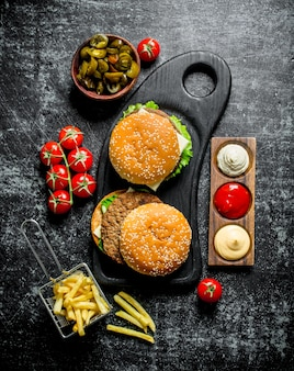 검은 시골 풍 테이블에 그릇에 감자 튀김, 토마토, jalapenos와 햄버거