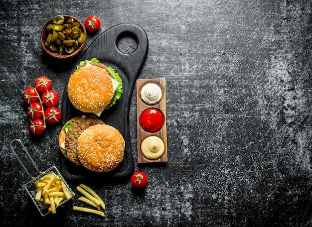 소박한 테이블에 그릇에 감자 튀김, 토마토, jalapenos와 햄버거