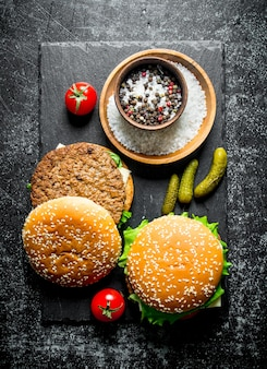 시골 풍 테이블에 향신료, 토마토, 오이와 햄버거