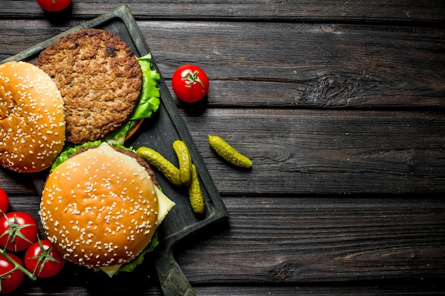 Burgers with tomatoes on a branch and gherkins. on black wooden background