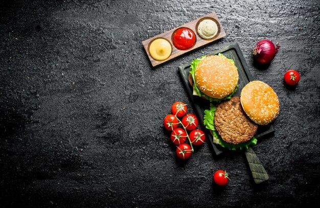 시골 풍 테이블에 토마토, 소스, 양파와 버거