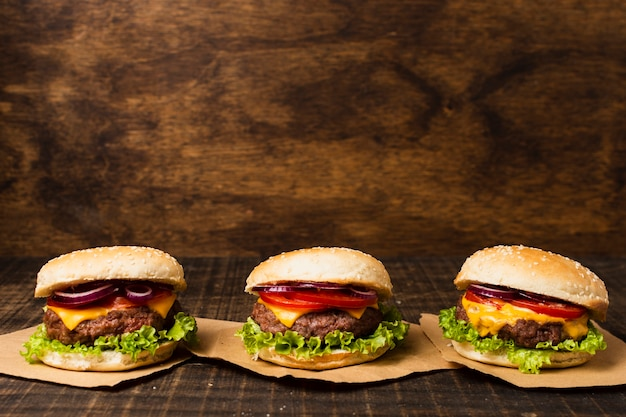 Burgers on wooden table with copy space