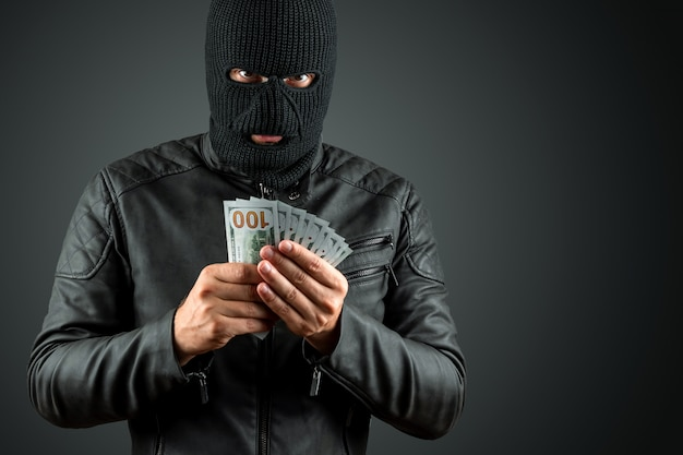 Burglar in a balaclava holds dollars in his hands on a dark background