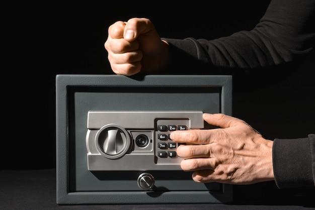 暗い背景に安全ボックスを壊す泥棒