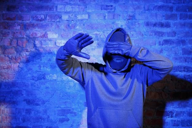 도둑은 밤에 벽돌 벽 근처에서 눈을 감고 가죽 장갑