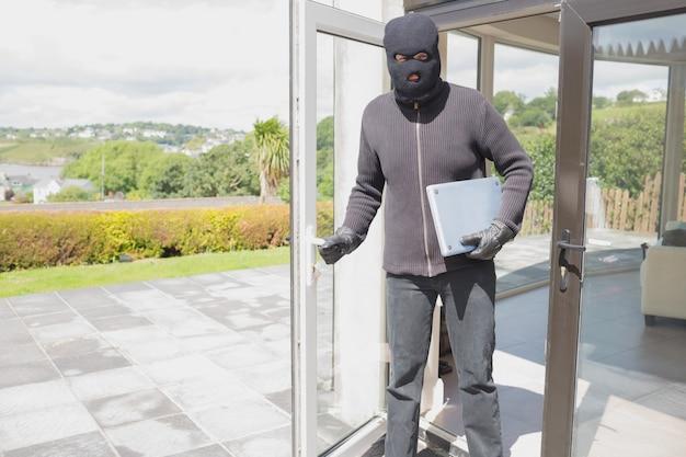 Взломщик, держащий ноутбук