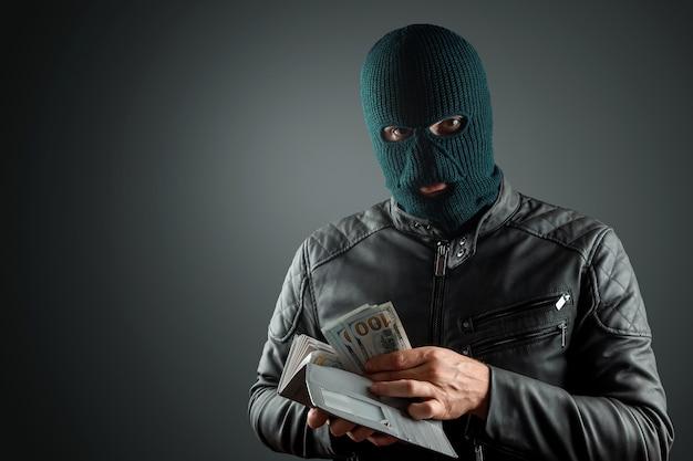 바라 클 라바에 강도 어두운 배경에 그의 손에 달러를 보유