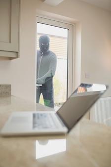 Взломщик смотрит на ноутбук через окно