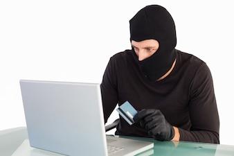 Burglar shopping online with laptop