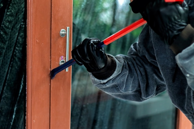 Burglar with crowbar trying break the door to enter the house