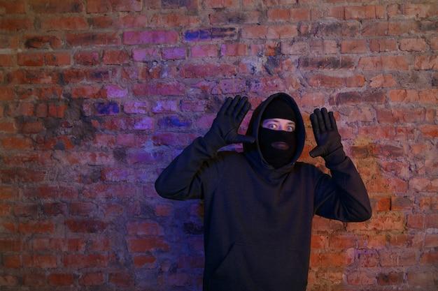 밤에 벽돌 벽에 손을 얹은 강도