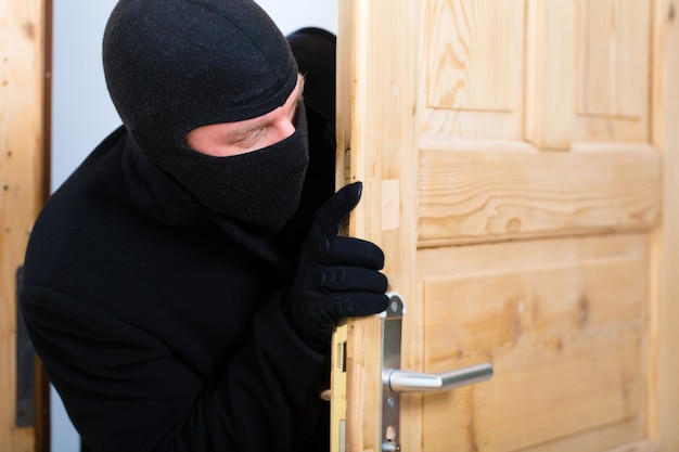 Кража со взломом - грабитель, открывающий дверь