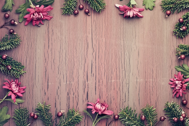 Burgundy chrysanthemum flowers on  textured background with winter decorations, copy-space