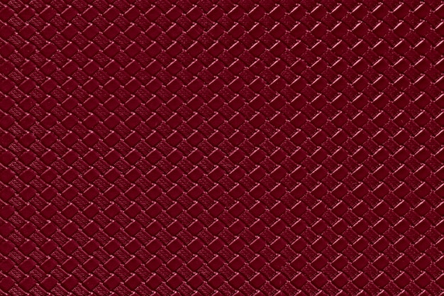 Burgundy leather background with imitation weave texture. glossy artificial leather structure.
